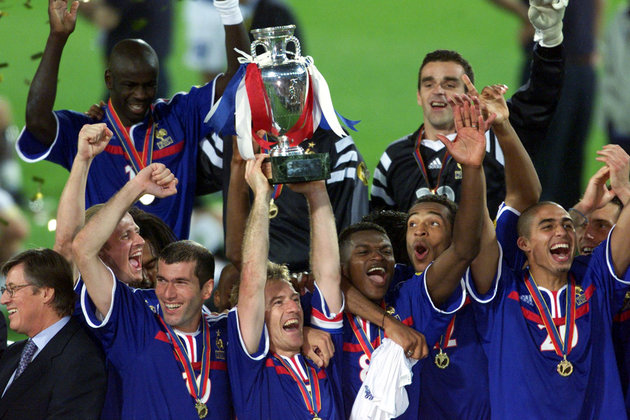 France's Didier Deschamps holds the winners trophy surrounded by teammates after  their victory [ove..