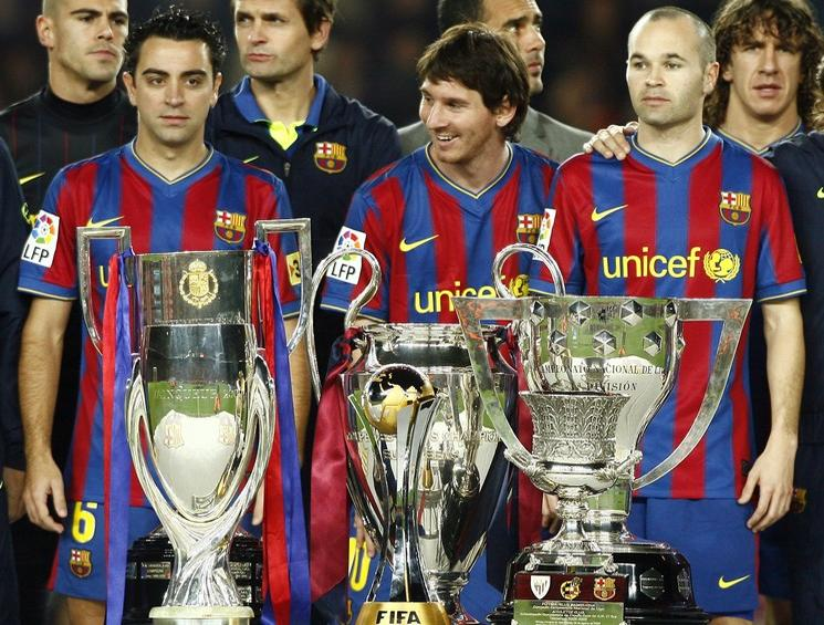 Barcelona's Hernandez, Messi and Andres Iniesta pose trophies won during the 2009 season, before Spanish first division soccer league match against Villarreal at Camp Nou stadium