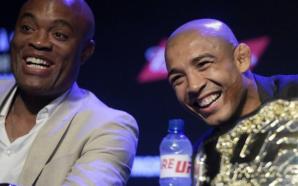 José Aldo e Anderson Silva estão sentados e rindo na bancada da entrevista coletiva do UFC 212